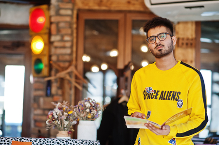 Asian man in eyewear and yellow sweatshirt posing indoor cafe with traffic light. Imagens - 121404987