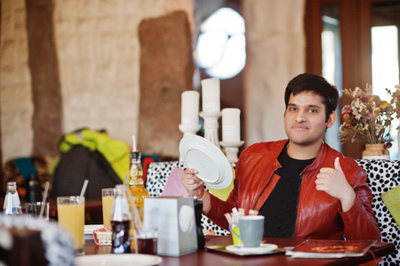 Stylish indian man in casual wear sitting indoor cafe and hold plate in hands.