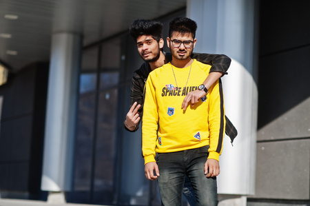 Two asian guys posed against new modern building.
