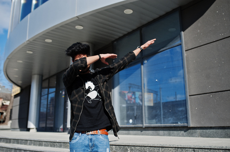 Beard asian man in casual wear posing against new modern building and show dab.