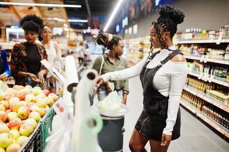 Group of african womans weighs apples in polyethylene bags at supermarket.