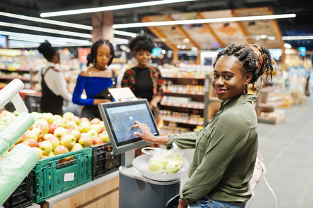 Un groupe de femmes africaines pèse des pommes dans des sacs en polyéthylène au supermarché.