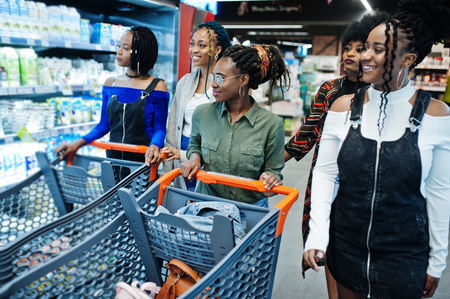 Group of african womans with shopping carts near refrigerator shelf selling dairy products made from milk in the supermarket. Фото со стока