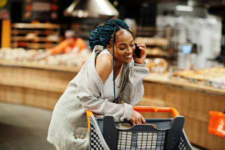 African american woman with shopping cart trolley in the supermarket store speak on mobile phone. Фото со стока - 122276693