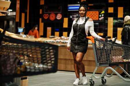 African american woman with shopping cart trolley in the supermarket store.