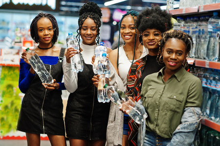 Group of five african womans with plastic bottles of water in supermarket.