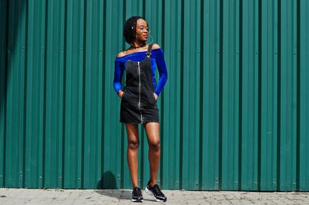 African woman in denim overalls skirt, eyeglasses posed against green steel wall.