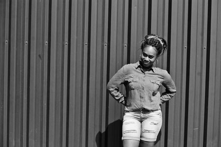 African woman with dreads hair, in jeans shorts posed against green steel wall.
