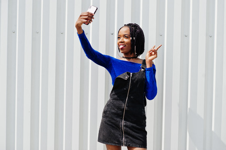 African woman in denim overalls skirt and blue dress posed against white steel wall and making selfie on phone. Imagens