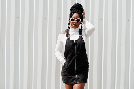 African woman in denim overalls skirt, white sunglasses posed against white steel wall.