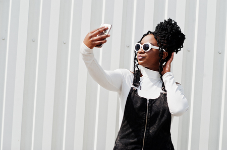 African woman in denim overalls skirt, white sunglasses posed against white steel wall and making selfie by phone.