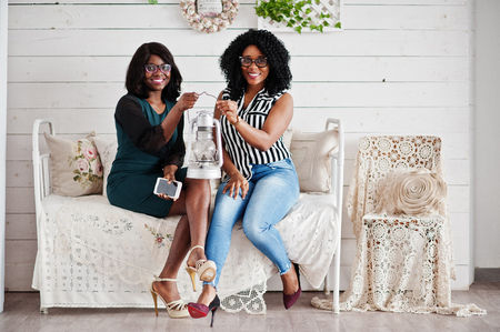 Two african woman friends wear on eyeglasses sitting at couch indoor white room. They hold old lantern together. Stock Photo