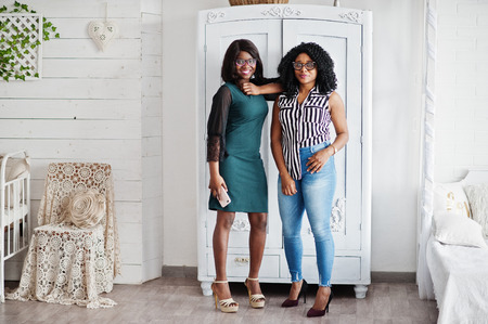 Two african woman friends wear on eyeglasses posed indoor white room against rustic wardrobe. One of them hold mobile phone at hand.