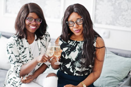 Two african woman friends wear on eyeglasses posed indoor white room and drink champagne from glasses.
