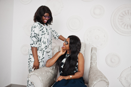 Two african woman friends wear on eyeglasses posed indoor white room. One of them sitting on soft chair.