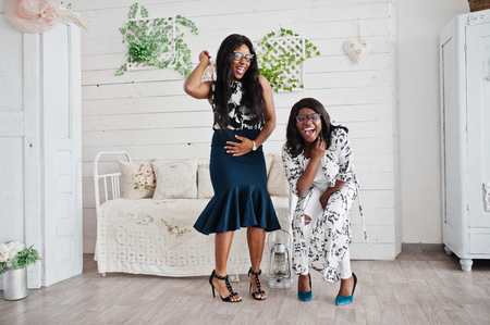 Two african woman friends wear on eyeglasses posed indoor white room. Laughing and having fun together.
