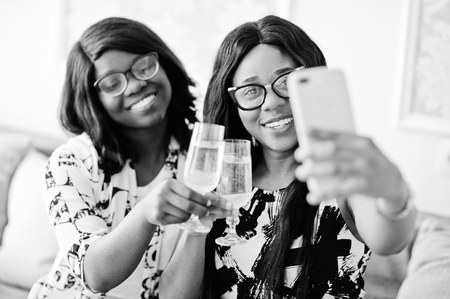 Two african woman friends wear on eyeglasses posed indoor white room, drinking champagne and making selfie. Imagens
