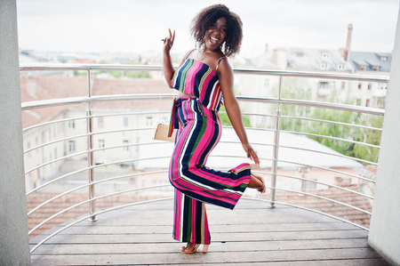 Fashionable and happy african american woman in pink striped jumpsuit, with handbag posed in the french balcony.