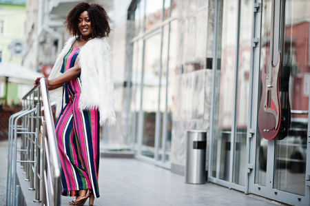 Fashionable african american woman in pink striped jumpsuit with fluffy faux fur coat posed at street of megapolis. Stock Photo