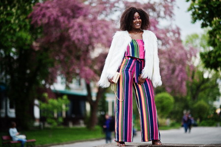 Fashionable african american woman in pink striped jumpsuit with fluffy faux fur coat posed at spring bloom street.