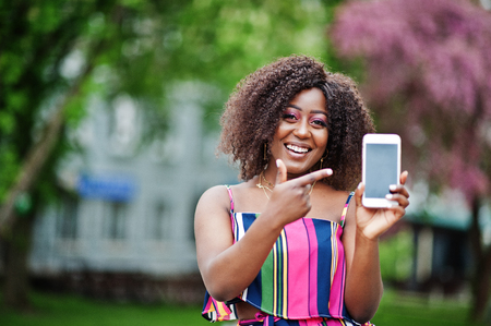 Fashionable african american woman in pink striped jumpsuit posed at spring bloom street and show finger to screen of cell phone.
