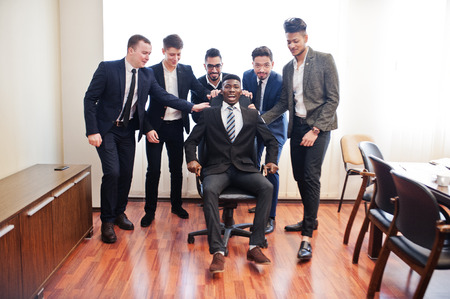 Six hommes d'affaires multiraciaux debout au bureau et roulent l'homme sur une chaise. Groupe diversifié d'employés masculins en tenue de soirée s'amusant.