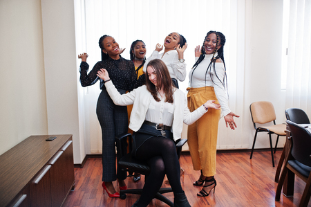 Five multiracial business womans standing at office and roll woman on chair. Diverse group of female employees in formal wear having fun. Фото со стока