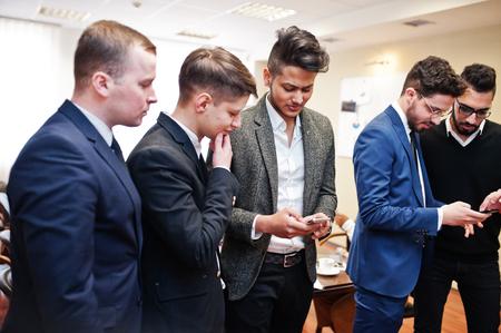 Zes multiraciale zakenmannen staan op kantoor en gebruiken mobiele telefoons. Diverse groep mannelijke werknemers in formele kleding met mobiele telefoons.