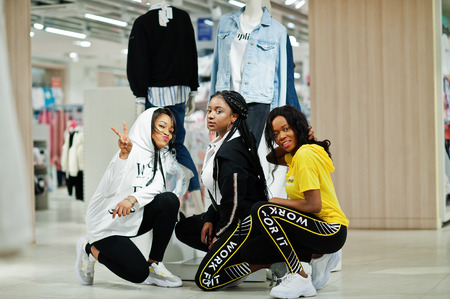 Three afican american women in tracksuits shopping at sportswear mall against mannequin. Sport store theme. Banque d'images