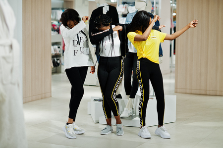 Three afican american women in tracksuits shopping at sportswear mall against mannequin. Sport store theme. Show dab.