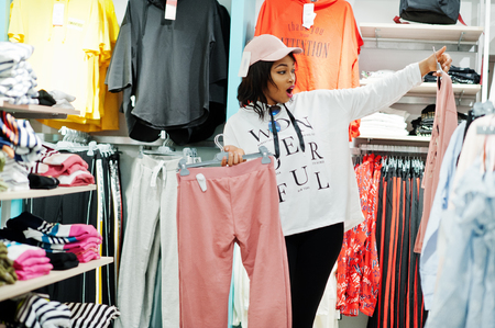 Afican american woman in tracksuits shopping at sportswear mall against shelves. Sport store theme.