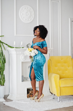 Afican american woman in brilliant glitter sequins turqoise dress, golden higheels standing with flowers against white room with yellow chair and fireplace.