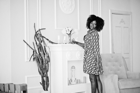 Fashionable tall african american model woman with red afro hair in dress posed at white room against yellow chair and fireplace.