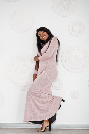 Fashionable african american model woman in pink brilliant evening dress posed against white decorative wall.