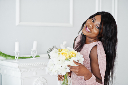 Fashionable african american model woman in pink brilliant evening dress posed with flowers vase on hands.
