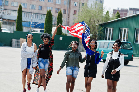 Group of five african american woman walking together on parking with USA flag.