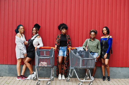 Group of five african american woman with shopping carts having fun together outdoor.