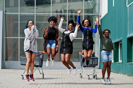 Group of five african american woman with shopping carts having fun together and jumping outdoor.