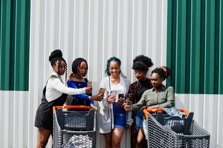 Group of five african american woman with shopping carts making selfie on mobile phone outdoor. 版權商用圖片