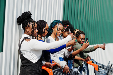 Group of five african american woman with shopping carts making selfie on mobile phone outdoor. Stockfoto