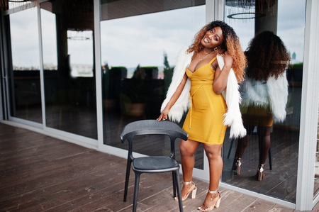 Glamour african american woman in yellow dress and white woolen cape standing near chair at terrace. Reklamní fotografie