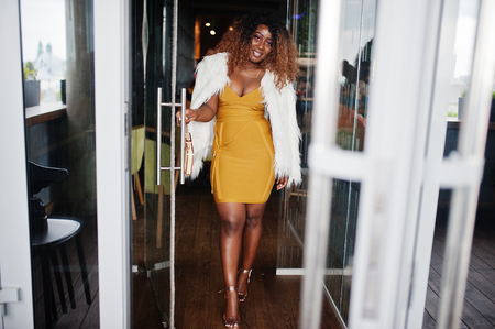 Glamour african american woman in yellow dress and white woolen cape with handbag posed at glass door entrance of restaurant. Reklamní fotografie