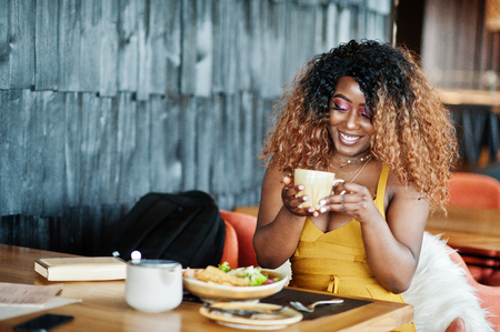 Glamour african american woman in yellow dress sitting on restaurant with cup of tea.
