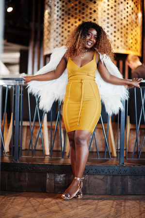 Glamour african american woman in yellow dress and white woolen cape posed at restaurant. Banco de Imagens - 122674075