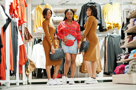 Three attractive african american woman in brown tunic dress posed at clothes store with handbags. Its time for shopping.