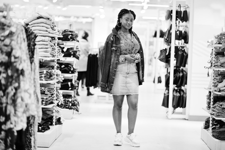 Modish african american woman in  red shirt and jeans skirt with jacket posed at clothes store. Its time for shopping.