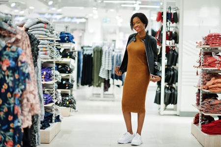 Thin african american woman in brown tunic dress and black leather jacket posed at clothes store. It's time for shopping.