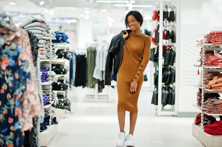 Thin african american woman in brown tunic dress and black leather jacket posed at clothes store. Its time for shopping. 版權商用圖片