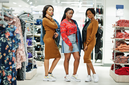 Three attractive african american woman in brown tunic dress posed at clothes store. It's time for shopping. 免版税图像
