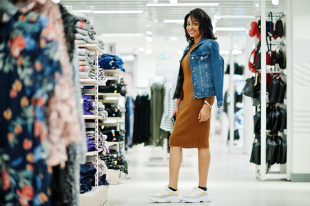 Chic african american woman in brown tunic dress and jeans jacket posed at clothes store. It's time for shopping.